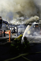 1992 File Photo Montreal (Quebec) CANADA<br /> Firemen create a rainbow  while theyr direct the water jet toward a burning old factory buiding,  No model release<br /> Photo (c) P Roussel / Images Distribution