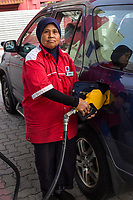 Muslim Female Gas Station Attendant Pumping Gas, Ipoh, Malaysia.