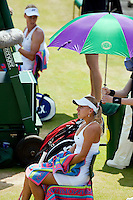 29-6-09, England, London, Wimbledon, Elena Vesnina is protected for the sun by a ambrella during changeover in her match against Dementieva in the background
