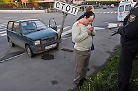Moscow, Russia 13/05/2007..A policeman watches as a member of an ambulance crew helps a drunken driver from his car after he crashed into a stop sign at at a road junction. The man was uninjured but was so drunk he could not walk without assistance.