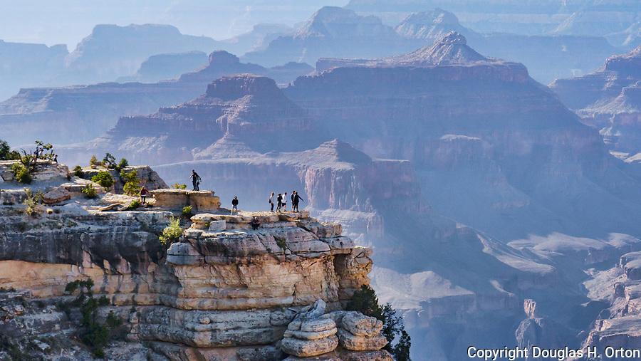 Tourists venture beyond the viewpoint railing at Grand Canyon National Park, Arizona, USA