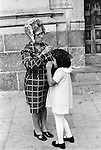 Mazatlan Mexico 1970s. Mother and daughter outside Roman Catholic church getting ready. Mother is fixing her daughters head covering a mantilla before they go into the church. 1973