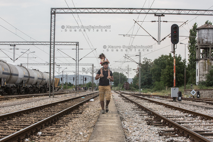 migrante con bambina sulle spalle cammina lungo la  ferrovia  migrant with a child on his shoulders walking along the railroad 2015