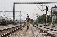 migrante con bambina sulle spalle cammina lungo la  ferrovia  migrant with a child on his shoulders walking along the railroad 2015