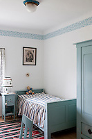 A children's bedroom with a pastel blue color palette and a Madonna and child print hanging above the bed