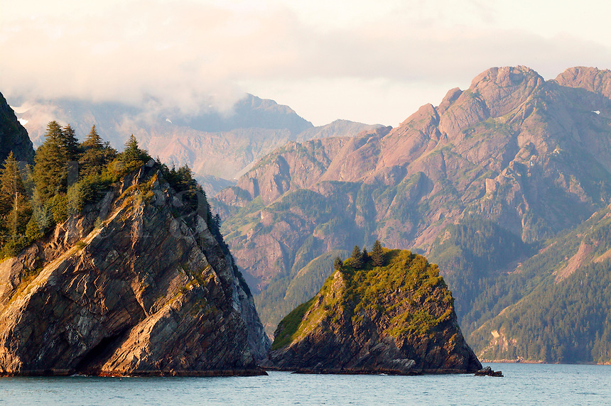 Sedimentary rock of the Pacific Plate in the foreground with pillow basalt rock on the North American Plate in the background, Resurrection Bay, Alaska.  In the ocean between the two plates is the subduction zone in which the two plates meet.  This is one of the most seismic active place in the world