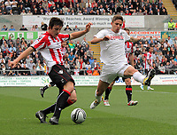 Pictured L-R: Harry Maguire of Sheffield marked by Fabio Borini of Swansea. Saturday 07 May 2011<br />