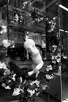 Switzerland. Zürich. Window of a hairdresser's salon. A baby doll fully naked and a wreath of flowers.  © 1992 Didier Ruef