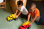 Education preschool 3-4 year olds two boys playing together with toy trucks