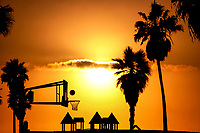 Mythic Venice Beach during a colorful sunset, with basketball hoop, ball, and palm tree silhouettes in Los Angeles, California USA