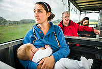 """A mother breastfeeding her baby of eight months on a land train at a visitor farm park.<br /> <br /> Image from the breastfeeding collection of the """"We Do It In Public"""" documentary photography picture library project: <br />  www.breastfeedinginpublic.co.uk<br /> <br /> <br /> Gloucestershire, England, UK<br /> 30/09/2013<br /> <br /> © Paul Carter / wdiip.co.uk"""