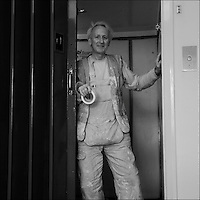 Man in decorators overalls in a lift.