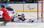 Sochi, RUSSIA - Mar 13 2014 - Kevin Rempel looks back as a shot rings off the post behind Steve Cash as Canada takes on USA in Sledge Hockey Semi-Final at the 2014 Paralympic Winter Games in Sochi, Russia.  (Photo: Matthew Murnaghan/Canadian Paralympic Committee)