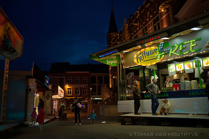 People line up for fries during a fair in the center of Geraardsbergen, Belgium on March 6, 2013. The fry stand displays words in Dutch, French and  English.