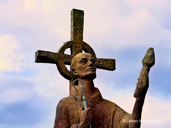 Red concrete statue of St. Aidan, who founded the monastery on the island of Lindisfarne in 635AD and spread Christianity amongst the Anglo-Saxon communities throughout the north of England. The statue was made by Kathleen Parbury, who died in 1986 and is buried nearby.