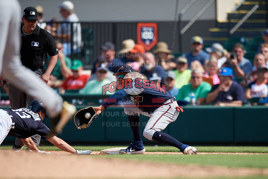 Atlanta Braves first baseman Johan Camargo (17) receives a pick off throw as Dustin Peterson (13) dives back towards the base as first base umpire James Hoye looks on during a Grapefruit League Spring Training game against the Detroit Tigers on March 2, 2019 at Publix Field at Joker Marchant Stadium in Lakeland, Florida.  Tigers defeated the Braves 7-4.  (Mike Janes/Four Seam Images)