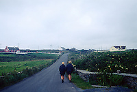 .Two girls walking on a country road, County Cork, Ireland