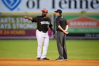 Chattanooga Lookouts manager Tommy Watkins (8) talks with first base umpire Anthony Perez during a game against the Jackson Generals on May 9, 2018 at AT&T Field in Chattanooga, Tennessee.  Chattanooga defeated Jackson 4-2.  (Mike Janes/Four Seam Images)