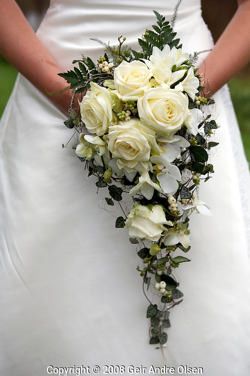Weddingflowers and white wedding-dress on the brides happiest day
