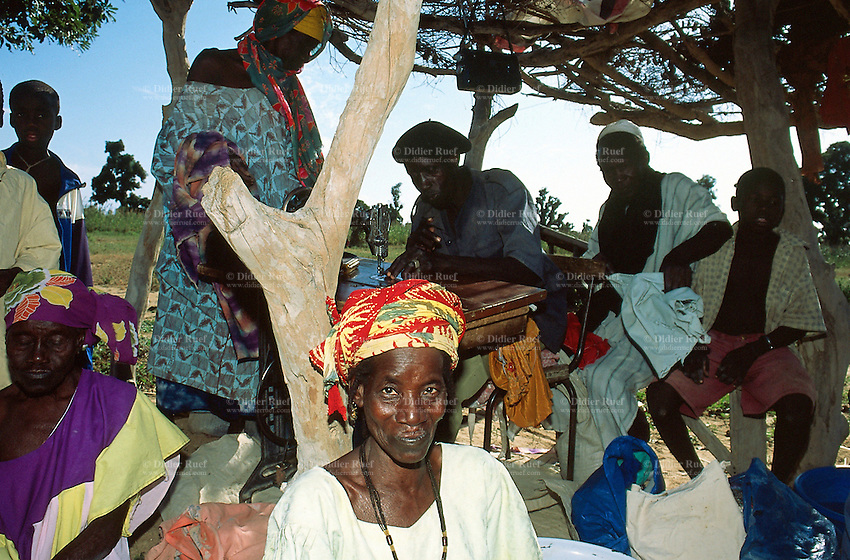 Mali. Province of Segou. Zambougou. An old woman  sells  clothes in the village's market.  A man works  on his sewing machine on the various fabrics for his customers. © 2003 Didier Ruef