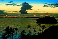 Sunrise and clouds over the still, dark lagoon and a motu in Bora Bora, beautiful, romantic honeymoon destination, near Tahiti, French Polynesia
