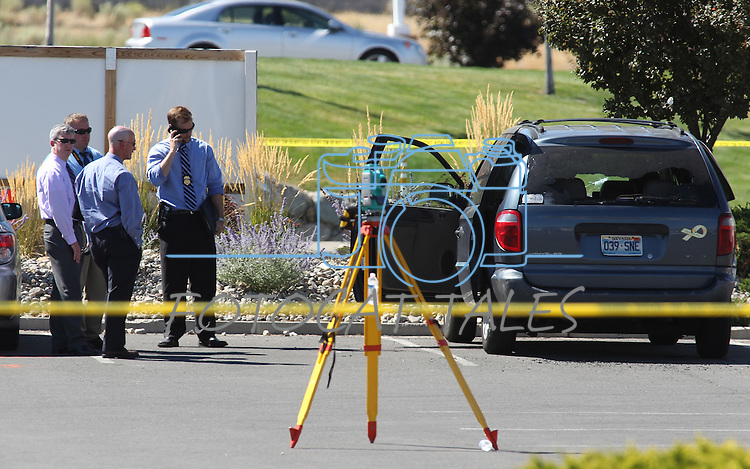 """Officials investigate the scene after a gunman opened fire with an AK-47 in an IHOP restaurant in Carson City, Nev., on Tuesday, Sept. 6, 2011. The gunman killed three people, including two Nevada National Guard members, and injured six others before shooting himself. The suspect's van, right, has a """"Support Our Troops"""" magnet on the rear. (AP Photo/Cathleen Allison)"""