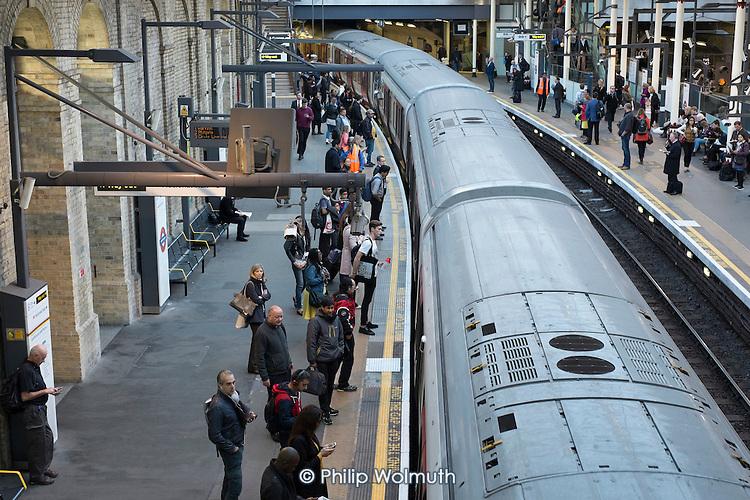 London rush hour passengers and trains at Farringdon underground station