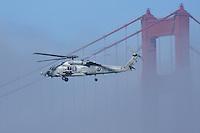 A U.S. Navy UH-60 Sea Hawk flies near one of the Golden Gate Bridge towers.