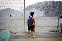 """CHINA. Beijing. A woman peers through a fence, trying to catch a glimpse of the new Olympic park. In recent years construction has boomed in Beijing as a result of the country's widespread economic growth and the awarding of the 2008 Summer Olympics to the city. For Beijing's residents however, it seems as their city is continually under construction with old neighborhoods regularly being razed and new apartments, office blocks and sports venues appearing in their place. A new Beijing has been promised to the people to act as a showcase to the world for the 'new' China. Beijing's residents have been waiting for this promised change for years and are still waiting, asking the question """"Where's the new Beijing?!"""". 2008"""