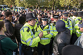 Police surround a heated debate between Muslims and islamophobic Tommy Robinson supporters, before escorting a speaker out of the park.  Speakers' Corner, Hyde Park, London.