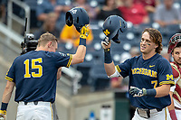 Michigan Wolverines outfielder Jesse Franklin (7) is greeted by teammate Jimmy Kerr (15) after his first inning home run against the Florida State Seminoles during the NCAA College World Series on June 17, 2019 at TD Ameritrade Park in Omaha, Nebraska. Michigan defeated Florida State 2-0. (Andrew Woolley/Four Seam Images)