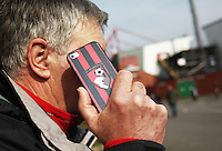 A Bournemouth fan talks on a phone with an AFC Bournemouth case on before the Barclays Premier League match between AFC Bournemouth and Swansea City played at The Vitality Stadium, Bournemouth on March 11th 2016