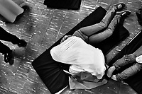 A Colombian believer, hugged by a female missionary, lies on the ground during the religious healing ritual performed by pastors of Misioneros Marianos church in Bogota, Colombia, 1 July 2013. Hundreds of Christian belivers, joined in nameless groups, gather every week in unmarked home churches dispersed in the city outskirts, to carry out prayers of liberation and exorcism. Community members and their religious activities are usually conducted by a charismatic pastor or preacher. Using either non-contactive methods (reading religous formulas from bible, displaying Christian symbols and icons) or rough body-pressure-points techniques and forced burping, a leading pastor commands the supposed evil spirit, which is generally believed to come from witchcraft, to depart a person's mind and body. The demon's expulsion often consists of multiple rites and may last for several months.
