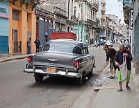 Cuba, Havana.  Early Morning Central Havana Street Scene.  Haling a Cab.