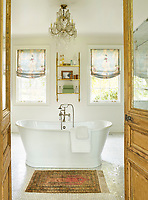 In the cool, white bathroom, the soaking tub is smack in the centre of the room. An antique rug is used as a bath mat and a pair of reclaimed doors from France round out the room.