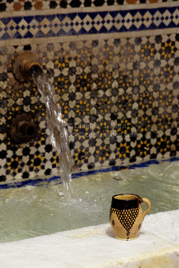 Fez, Morocco - A Cup Provided by an Anonymous Benefactor Awaits Passersby at the Nejjarine Fountain, in the Medina of Old Fez.