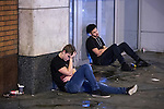 """© Joel Goodman - 07973 332324 . 17/12/2016 . Manchester , UK . Two men slouch on the pavement on Withy Grove . Revellers out in Manchester City Centre overnight during """" Mad Friday """" , named for being one of the busiest nights of the year for the emergency services in the UK . Photo credit : Joel Goodman"""