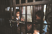 Qi Qi, 3, male (left) and Gwen Gwen, 5, are kept in a cage in a village house belonging to their uncle.  The children's parents are both in prison and the uncle is too poor to afford child care for the children and are afraid they may be stolen and are afraid they may be stolen a common problem in China...PHOTO BY SINOPIX