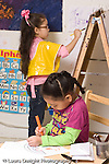 Education preschool 4 year olds art activity girl drawing in foreground while girl paints at easel in background vertical