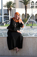 Tripoli, Libya, North Africa - Modern Libyan Woman's Clothing Style as seen in Public Park near the Green Square, downtown Tripoli.  Talking on Cell Phone.