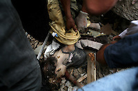 Beirut, Lebanon, Aug 13 2006.Rescuers unearth the body of a 9 year old girl from the rubble. A massive Israeli Air Force bombing raid destroyed 11 building blocks in the southern Beirut neighbouhood of Rwaiss, including the Imam Hassan school, totally levelled by more than 20 powerful bombs; more than 20 people, including children playing in the area are said to have lost their lives as a result of this 11th hour Israeli operation..