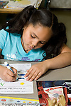 Education Elementary school Grade 2 foreign language female student working on Spanish language worksheet vertical