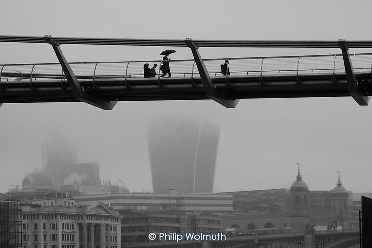 Man with an umbrella crosses the Thames Millenium Bridge in heavy mist.