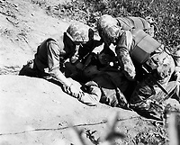 In bitter fighting on Hook Ridge, Marines threw back 800 screaming, bugle-blowing Chinese.  A wounded Marine is given a drink of water by buddies as he lies awaiting evacuation to a rear area aid station.  November 1952.  T.Sgt. Robert Kiser.  (Marine Corps)<br /> Exact Date Shot Unknown<br /> NARA FILE #:  127-N-A166426<br /> WAR & CONFLICT BOOK #:  1447
