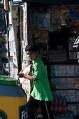 Ica, Peru. Boy (Peruvian) on errand has just purchased newspaper at newspaper stand on city street. No MR. ID: AL-peru.