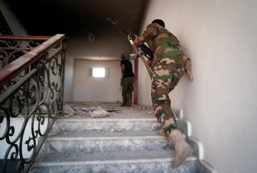 Anti-Gaddafi fighters search a building for Gaddafi loyalists in Sirte, Libya.