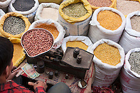 Kathmandu, Nepal.  A Market Vendor of Rice, Beans and Grains, Durbar Square, Weighs a Sale of Peanuts.