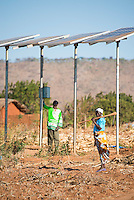 MALAWI, village Zingiziwa, solar powered water pump for irrigation and water supply in village, woman with hoe / MALAWI, Dorf Zingiziwa, Solar Pumpe foerdert Wasser fuer Bewaesserung und Wasserversorgung im Dorf, Frau mit Hacke