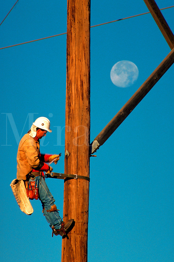 A utility worker on a power line pole with a daytime full moon.