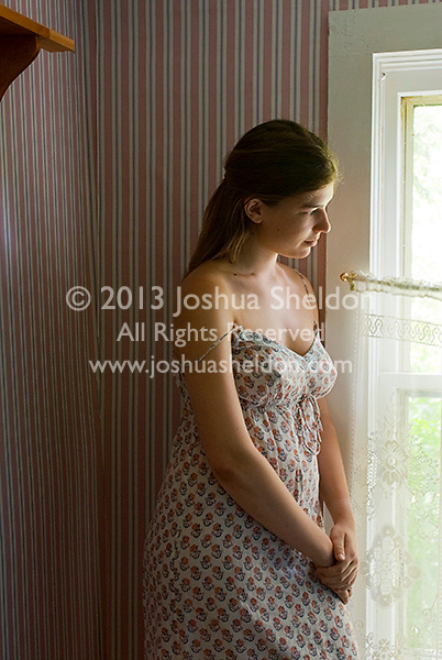Woman standing looking out window